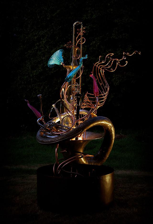 Musical instrument fountain sculpture created from copper tubing, a water wheel, blown glass, a musical scroll, repurposed brass and copper, and upcycled musical instruments including a sousaphone, a sax and a trumpet.