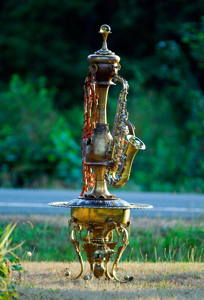 A human form sculpture playing a saxophone. Made from copper and brass upcycled pieces.