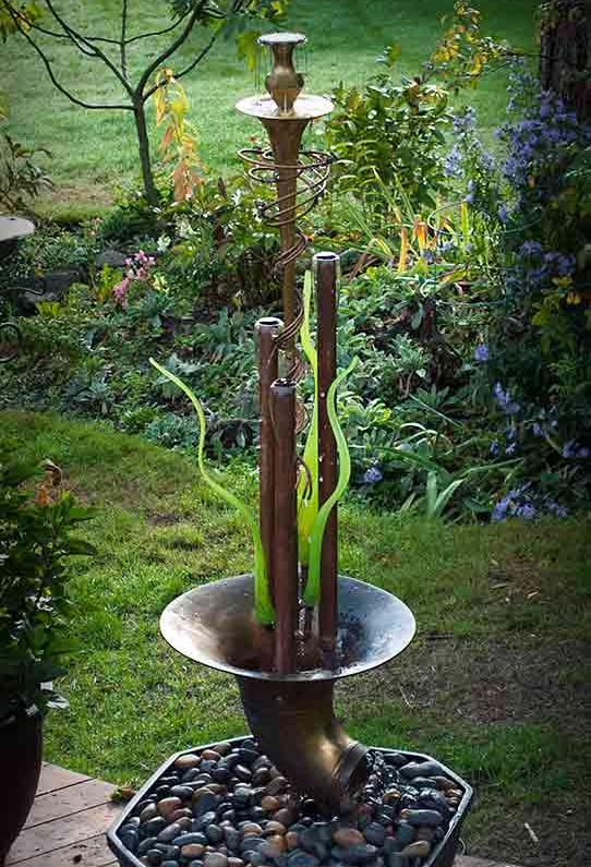 This fountain comprises three large copper tubes and three hand blown glass reeds centered in a tuba bell.  Water flows up and over the copper tubes forming water bells. It comes complete with water reservoir and pump and is currently available for purchase @ $ 2,400. Please call or email for further info and shipping details.